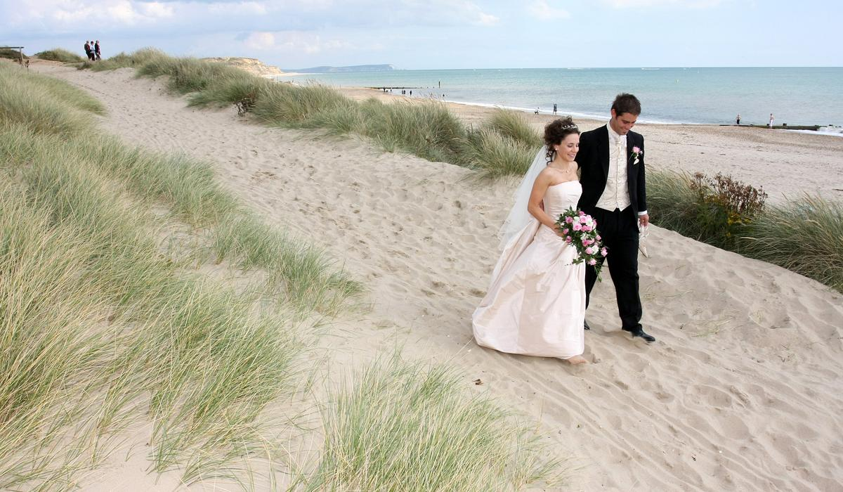 Bride and Groom walking hand in hand on a beach
