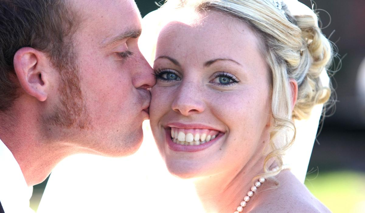Groom kissing bride on the cheek with bride smiling into the camera